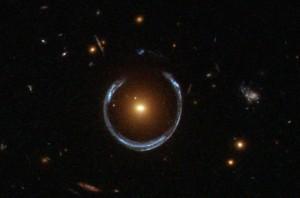 Eine rötlich/gelbliche Galaxie im Vordergrund lenkt durch ihre Masse Licht von einer hinter ihr liegenden, bläulichen, Galaxie ab was in der beobachteten Hufnagelform resultiert. Ein durch das Hubble Teleskop beobachtetes Beispiel für den durch die allgemeine Relativitätstheorie vorhergesagten Gravitationslinseneffekt. A Horseshoe Einstein Ring from Hubble by Lensshoe_hubble.jpg: ESA/Hubble & NASAderivative work: Bulwersator (talk) - Lensshoe_hubble.jpg. Licensed under Public Domain via Commons.